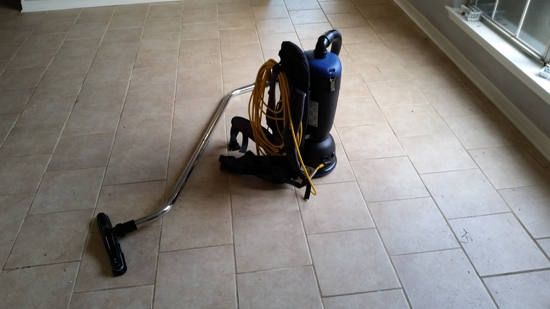 Picture of a backpack vacuum used to vacuum the tile and grout before cleaning