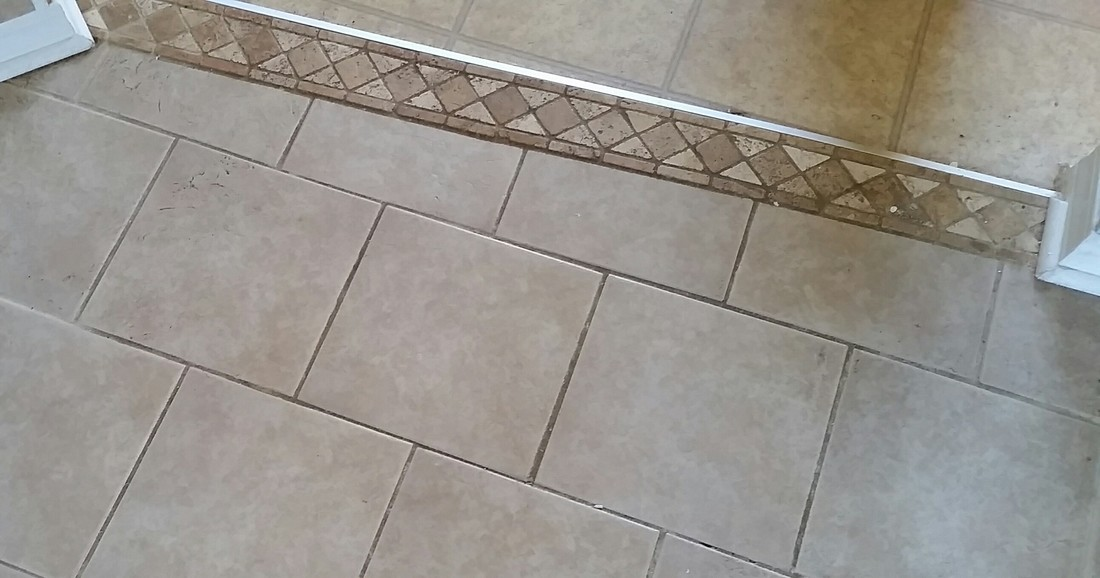 Picture of tile and grout before cleaning by the kitchen entrance where it receives a lot of high traffic