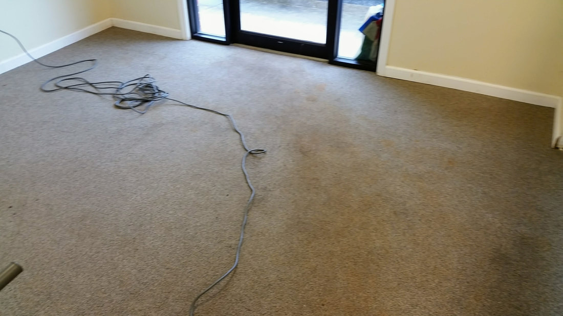 This is a picture of a commercial carpeting in the office area of a warehouse before cleaning. It shows the degree of soiling and red clay stains that have been tracked in